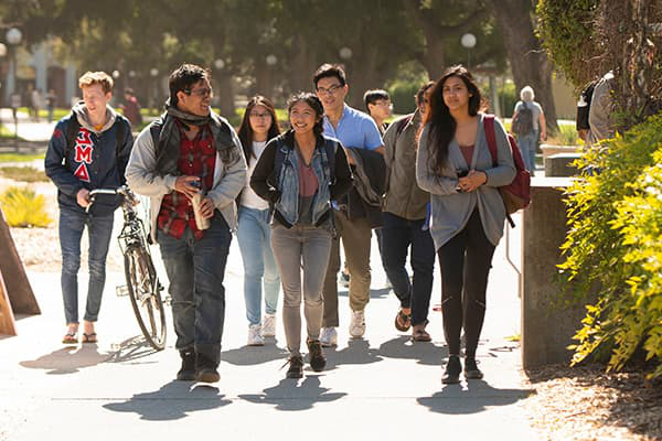 a group of students walking across campus - plan your transfer