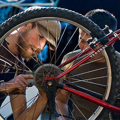 Two men repairing a bicycle wheel