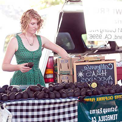 Woman at avocado stand setting it up